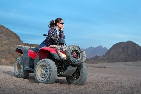 Pretty girl on atv on the desert sunrise background photo