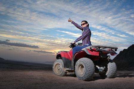 Pretty positive girl on atv on the desert sunrise background