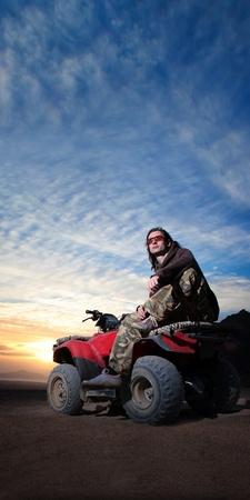 Smart man on atv on the desert sunrise background