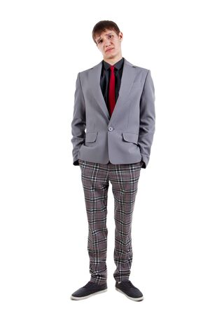 Funny disappointed student in checkered pants and suit. Isolated on white photo