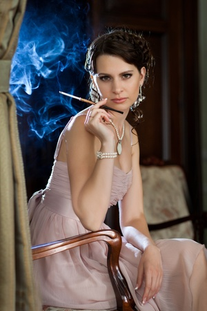Pretty woman is sitting on the chair and smoking cigarette. Blue smoke on the background. photo