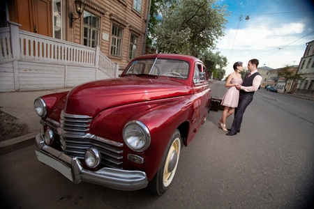 Pretty couple near the vintage car on the town background. Focus point on the car. Stock Photo