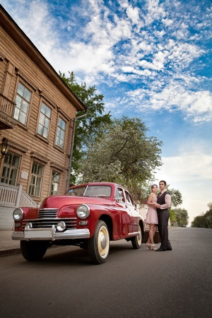 Pretty couple near the vintage car on the rural background. photo
