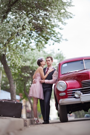 Pretty couple near the vintage car on the sunset background photo