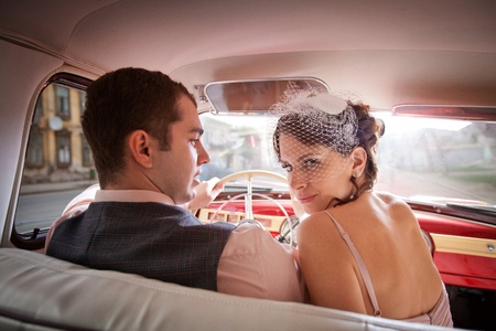 Pretty couple in the vintage car on the sunset background. photo