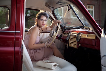 Pretty woman is sitting in the vintage car. photo