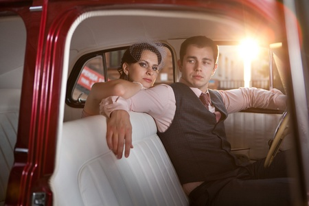 trip: Pretty couple in the vintage car on the sunset background.
