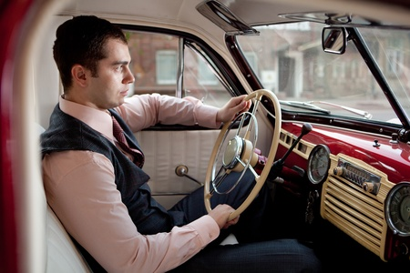 Man is sitting in the vintage car. photo