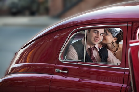 Pretty couple in the back seat of the vintage car. photo