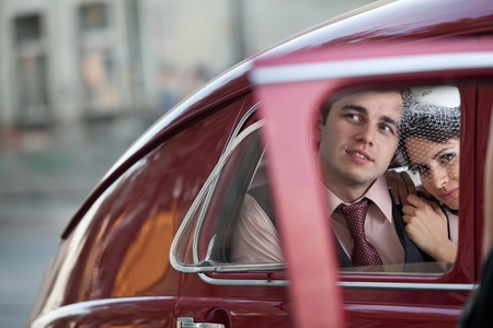 Pretty couple in the back seat of the vintage car.