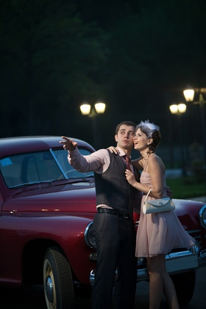 Pretty couple near the vintage car on the night city background photo