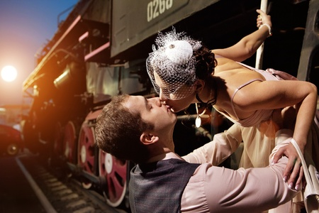 Greeting on the railway station. Man is kissing his lady.