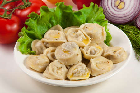 Tasty pelmeni with tomato and salad  Vegetables on the background  photo