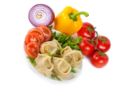 Tasty hinkali with tomato and salad. Vegetables on the background. Isolated on white. photo