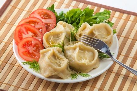 Tasty hinkali with tomato and salad. Stock Photo - 13684339