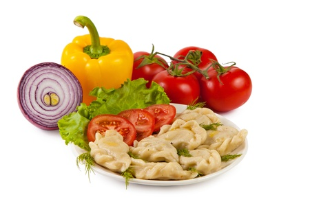 Tasty pelmeni with tomato and salad. Vegetables on the background. Isolated on white. photo