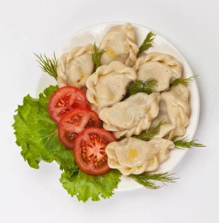 Tasty pelmeni with tomato and salad. photo