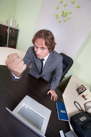 Angry businessman is shaking with his fist on the office background. photo