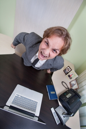 Angry shouting businessman on the office background. photo