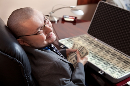 Serious businessman with the suitcase full of dollars is looking on the camera. Focus point on the face. Standard-Bild