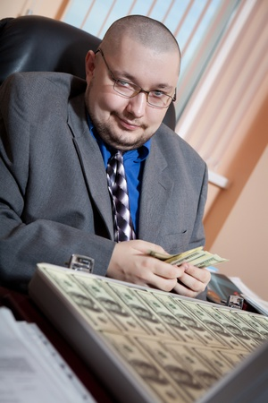 Serious businessman with the suitcase full of dollars is looking on the camera. Office background photo