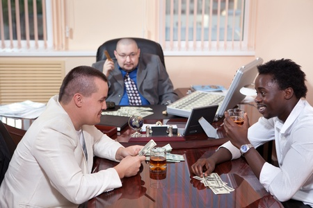 Gangsters in the office with the case of dollars. photo