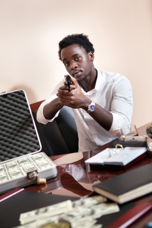 Robbery in the office.  Case of dollars on the background. photo
