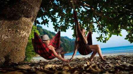 Pretty couple is laying on the hammocks on the tropical ocean background. photo