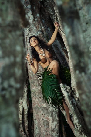 Indigene woman in the palm skirt, seashells necklace and coconut bra is holding lians Stock Photo - 18347238