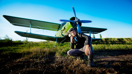Pilot is sitting in front of vintage plane  Rural background  photo