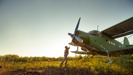 Pilot is starting engine of vintage plane  Rural background Reklamní fotografie - 22189398