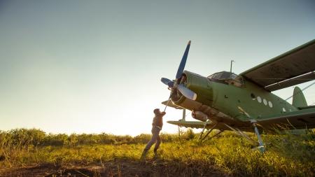 Pilot is starting engine of vintage plane  Rural background