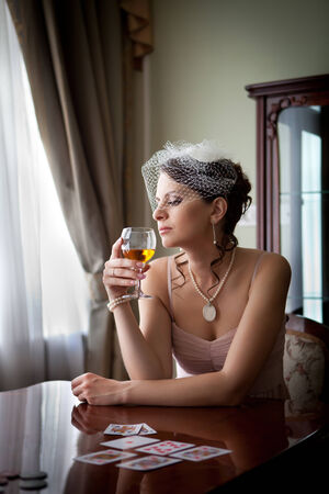 Woman in veil is playing poker with the glass of whiskey  photo