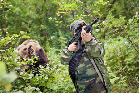 Yong hunter boy with the rifle is aiming and Wild bear  Stock Photo