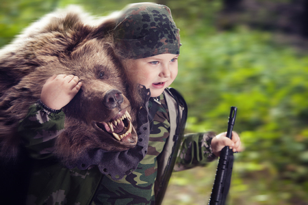 yong: Yong hunter boy with the rifle is holding a bear on the forest