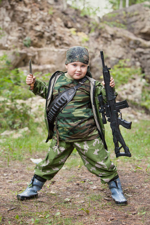 Yong hunter boy with the rifle is posing on the forest   photo