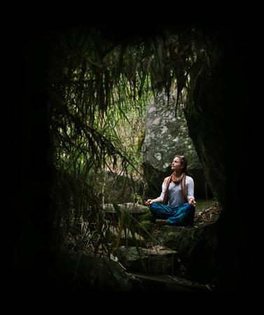 sfondo giungla: Yong donna a gambe incrociate relax sulla sfondo della giungla
