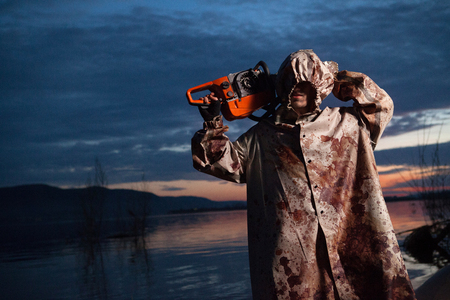 Maniac with the chainsaw dressed in a dirty bloody raincoat  Sunset river on the background photo