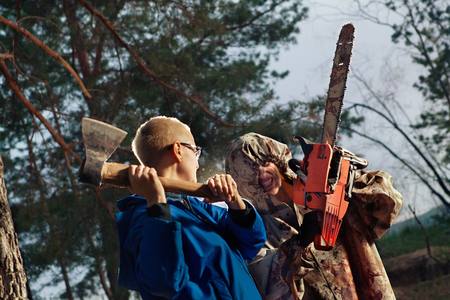 Woman fights with the maniac, axe against chainsaw photo