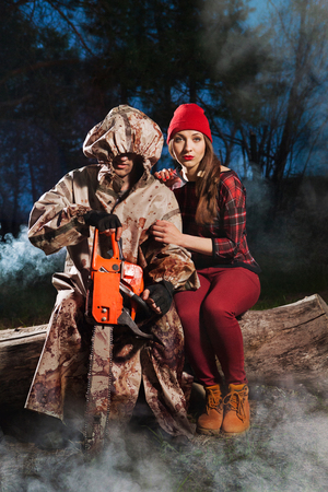 Maniac with the chainsaw dressed in a dirty bloody raincoat is sitting with the victim  photo