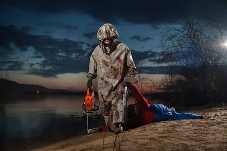 Maniac with the chainsaw dressed in a dirty bloody raincoat with the dead body photo