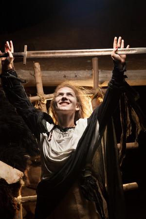 beldam: Pretty sorceress is making magic  Wooden den on the background  Stock Photo