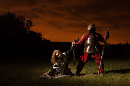 Medieval knight is going to make an execution of a witch photo