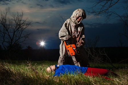 Maniac with the chainsaw dressed in a dirty bloody raincoat is killing the victim. photo