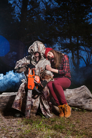Maniac with the chainsaw dressed in a dirty bloody raincoat is sitting with the victim. photo