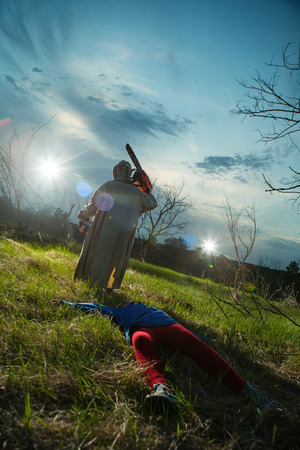 maniac: Maniac with the chainsaw dressed in a dirty bloody raincoat. Victim on the foreground, sunset forest on the background.