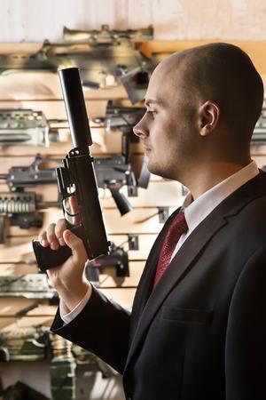 sicario: Hitman calva con la pistola en el fondo de la pared armer�a.
