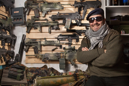 Arms merchant in the beret and sunglasses on the weapon display background