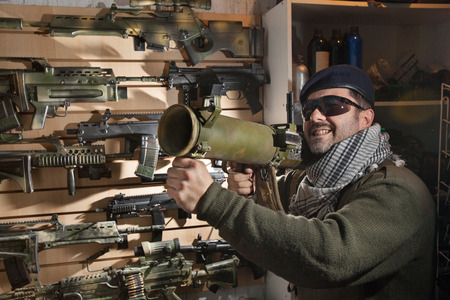 separatist: Arms merchant in the beret and sunglasses with the jet grenade launcher on the weapon display background Stock Photo