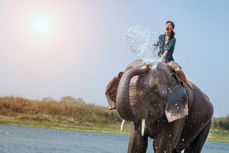 Hermosa chica está teniendo una ducha con el elefante. Foto de archivo